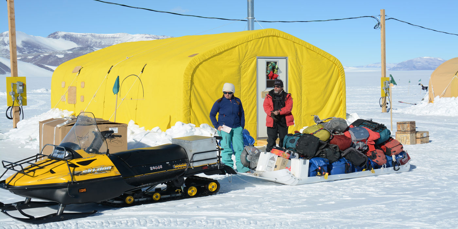 a woman and man stand with a snowmobile sled filled with gear