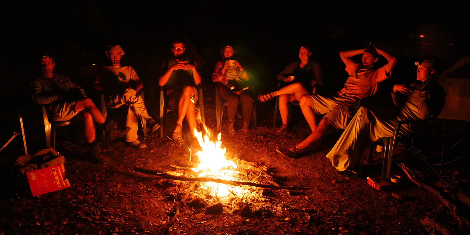 The group sitting around a campfire at night
