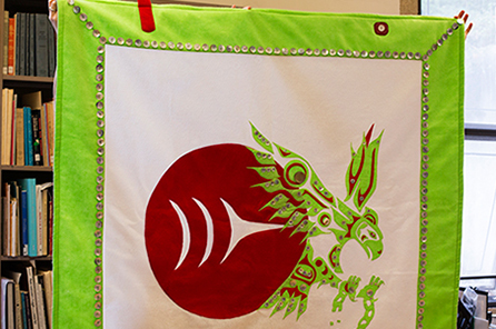 A button-blanket with green, white and red colors includes the Burke Museum logo and an eagle breaking out of chains