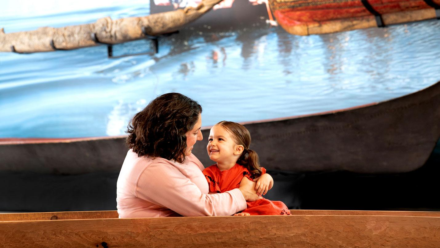 a mom and daughter sit in a boat in the gallery