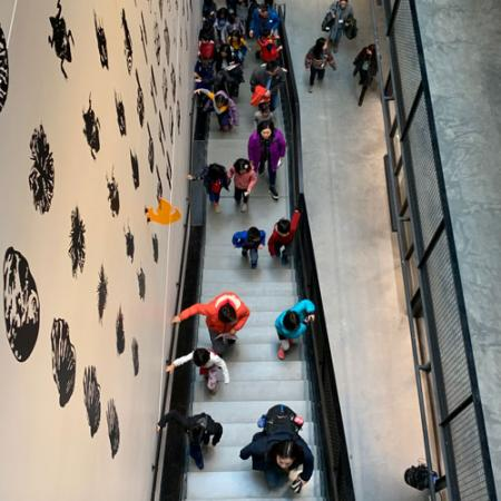 a group of children run up the stairs inside the new burke museum