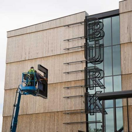 Two crew members use a lift to install the letter E on the new Burke sign