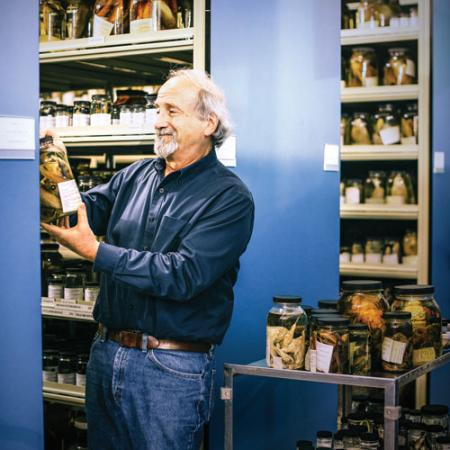 A male researcher among shelves of fish collections holds a jar containing a fish specimen