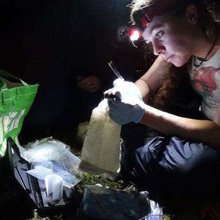 a young woman wears a headlight and holds a bat while working in the field at night