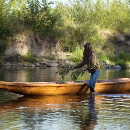 a young woman lays cedar branches in a cedar canoe in the water