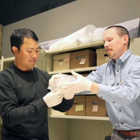 Two men wear gloves while removing an archaeological artifact from its bag