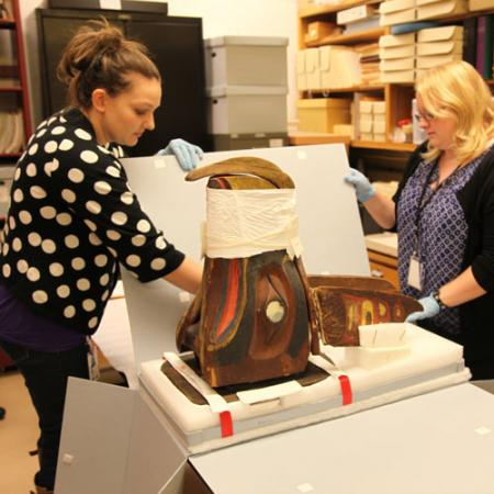 Two woman carefully unpack the native art mask from a box