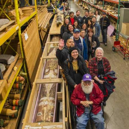 A large group stands next to the story pole after it arrived in its shipping crate to the Burke Museum collections.