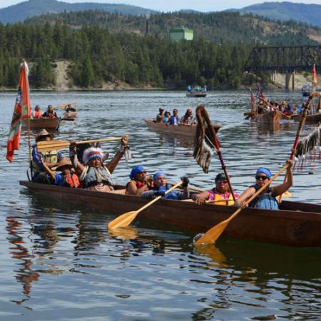 A group of people in traditional native clothes paddle a canoe