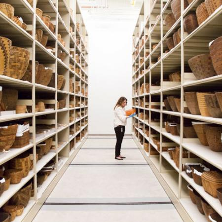 a woman stands in a row of basketry on collections shelves