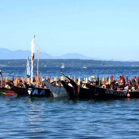 A group of decorated tribal canoes in the water with people inside the canoes
