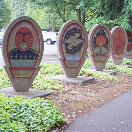 Six spirit board sculptures outdoors depicting art in the Coast Salish style