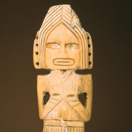 A carved figure with its arms crossed and wearing a headdress