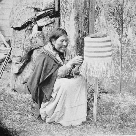 a woman sits and weaves a basket on a post