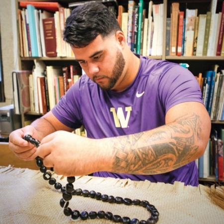 A male student in purple UW Husky tee shirt holding a beaded necklace alongside a woven Samoan rug