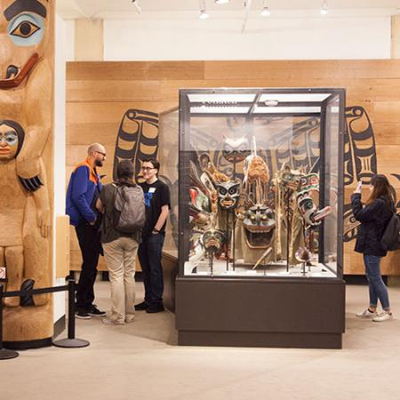 People inside of a museum exhibit surrounded by native art