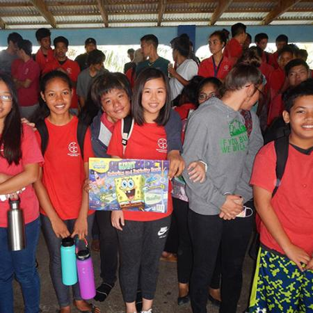A group of schoolchildren wearing backpacks hold a picture of Spongebob Squarepants