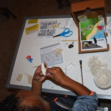 a child makes a clay tooth necklace in the fossil finder fun pack box from the Burke Museum