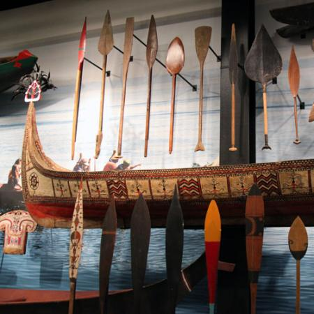 a canoe hangs on a wall with many paddles on display next to it
