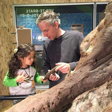 a man shows a girl a fossil while the stand in front of the t.rex skull