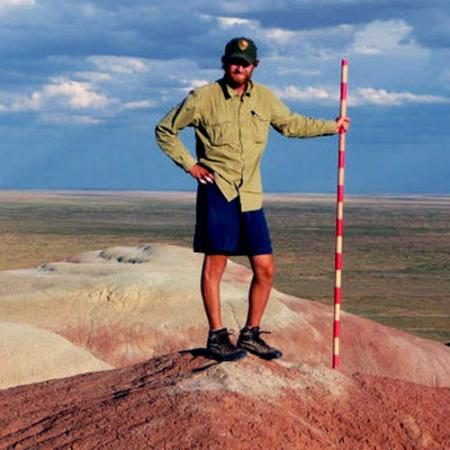 A male researcher stands in the Wyoming desert holding a red and white striped pole