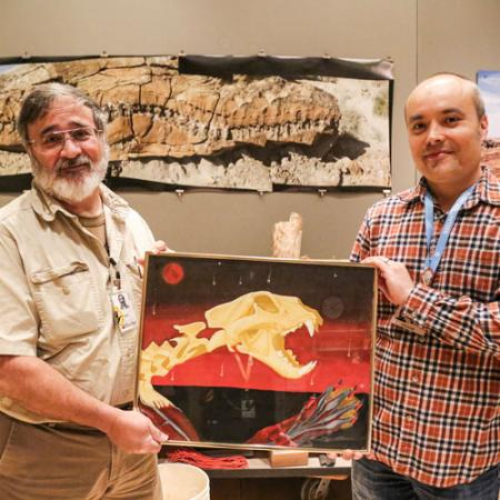 two men hold a scientific illustration in the burke's paleontology prep lab