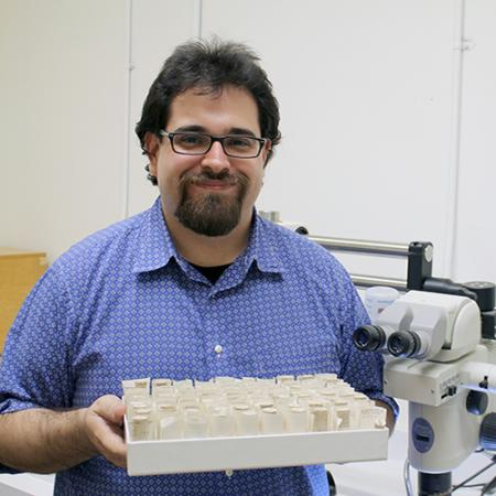 A male researcher holds a tray of tubes and stands next to a microscope