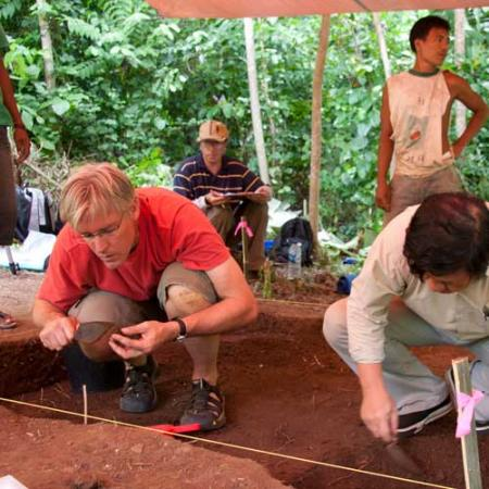 Two men kneel in an archaeological dig site and closely examine sediment for artifacts