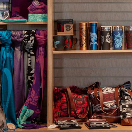 Scarves, mugs and bags on a shelf