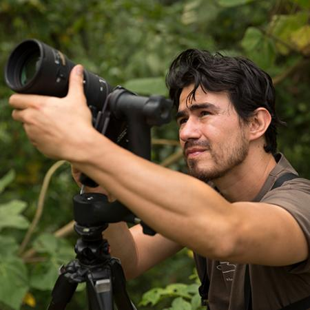 A man stands in the jungle holding a large camera