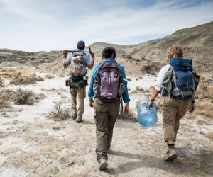 Three people with backpacks and palentology equipment walking in the desert